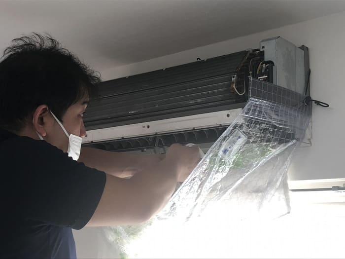 エアコンを拭き上げるおそうじ本舗スタッフ