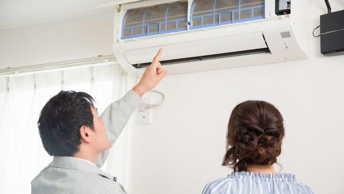 エアコン掃除の説明を受ける女性