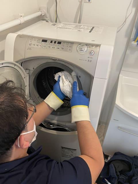 洗濯機の内側を拭き取るおそうじ本舗スタッフさん