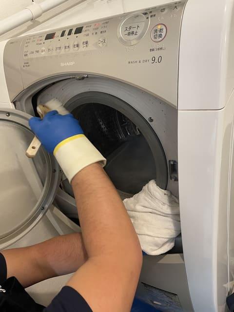 洗濯機のドア周辺を掃除するおそうじ本舗スタッフさん