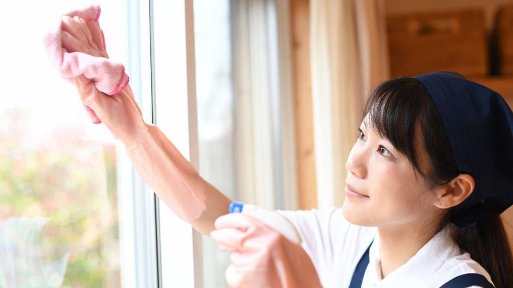 窓拭きする女性